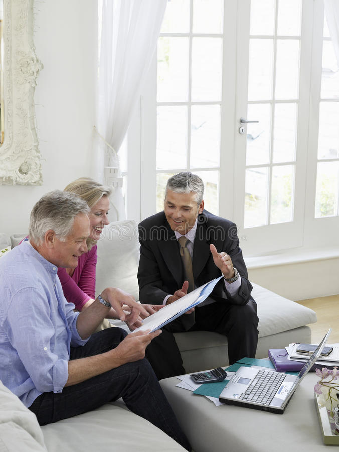 Paare mit Finanzberater am Sofa lizenzfreie stockbilder