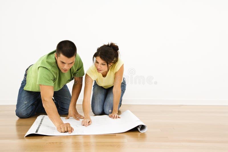Paare mit Hausplänen. lizenzfreie stockfotografie