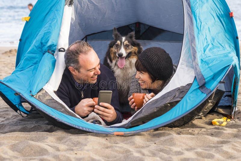 Paare mit Hund in einem Zelt unter Verwendung des Telefons stockfotografie