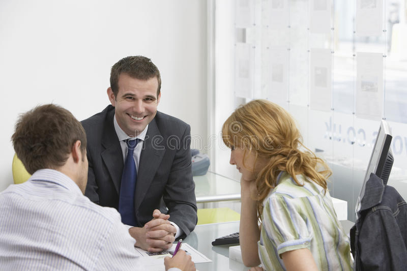 Paare mit Immobilienagentur In Office lizenzfreie stockfotos
