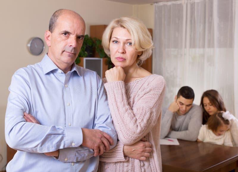 Paare mit Kind und Rechnungen bei Tisch und ältere Eltern stockfoto