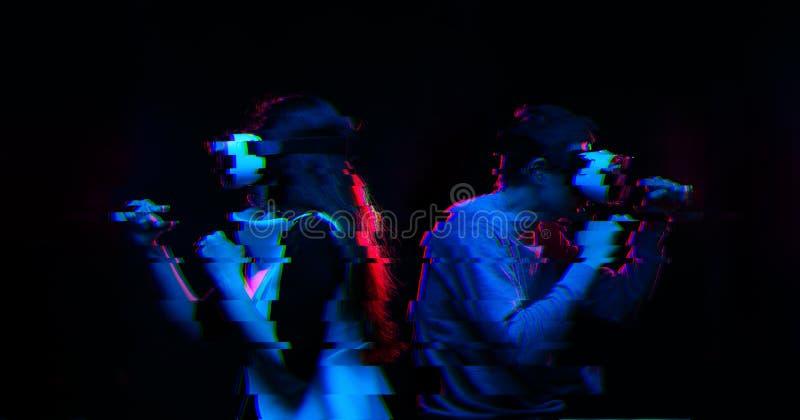 Paare mit Kopfh?rer der virtuellen Realit?t spielen Spiel und das K?mpfen Bild mit St?rschubeffekt lizenzfreie stockbilder