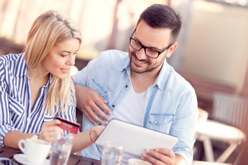 Paare mit Kreditkarte im Café, das digitales Tablette togeth betrachtet stockfotos