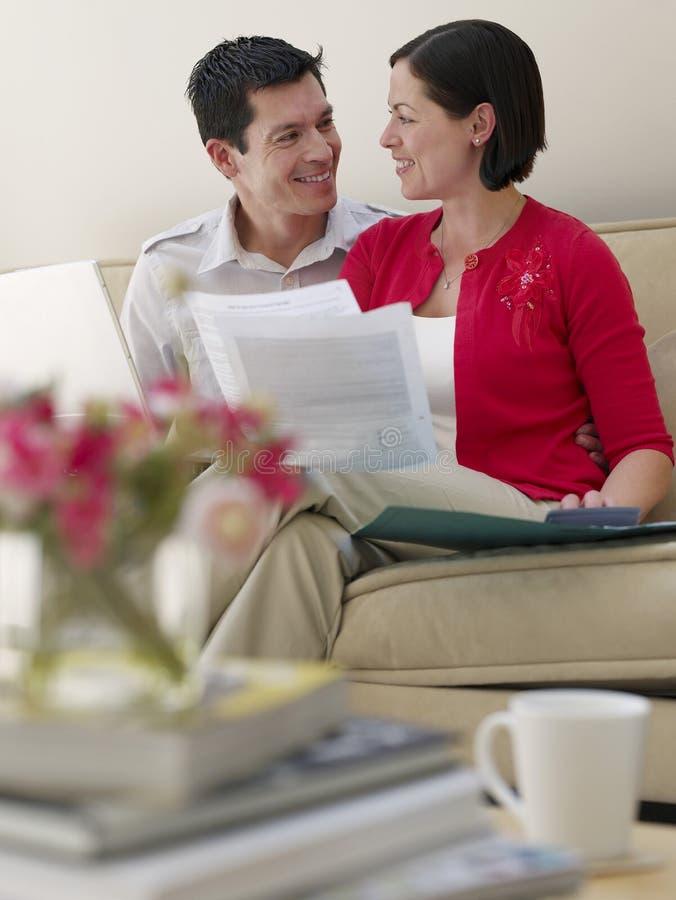 Paare mit Laptop und Rechnungen auf Sofa stockfotografie