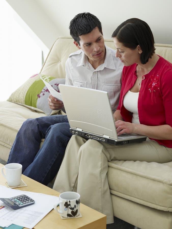 Paare mit Laptop und Rechnungen auf Sofa lizenzfreies stockfoto