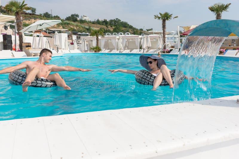 Paare mit Rettungsring im Swimmingpool stockbilder