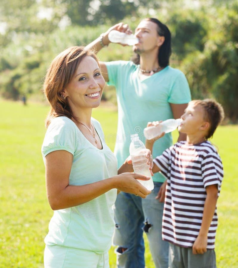 Paare mit Trinkwasser des Jugendlichen von den Flaschen lizenzfreies stockbild