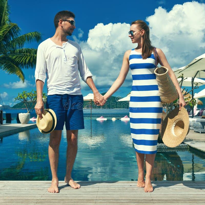 Paare nähern sich Poolside lizenzfreie stockfotografie