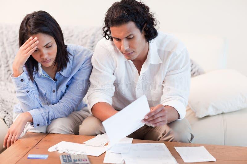 Paare niedergedrückt über Finanzprobleme lizenzfreies stockfoto