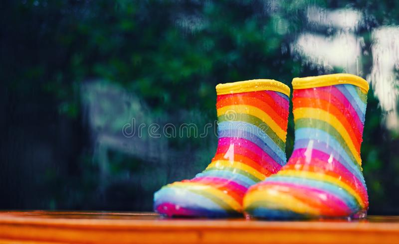 Paare Regenbogenregenstiefel, die draußen mit einem regnerischen unscharfen Heraushintergrund sitzen stockbilder