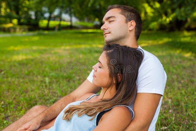 Paare schlafen während Picknick im Park ein lizenzfreie stockfotos