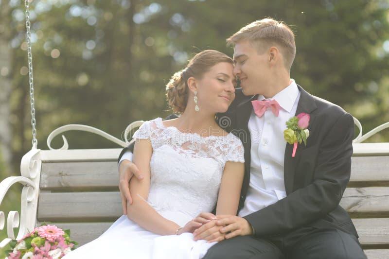 Paare sitzen auf Bank im Park lizenzfreie stockbilder
