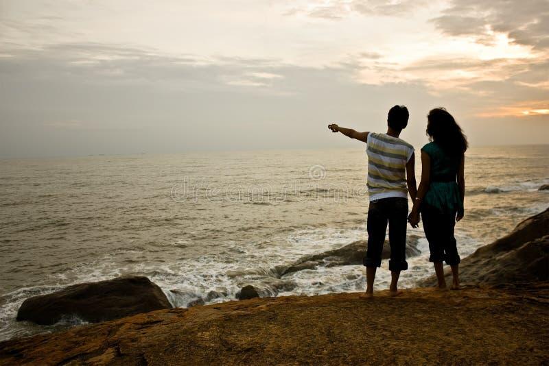 Paare am Sonnenuntergang auf dem Strand stockbild