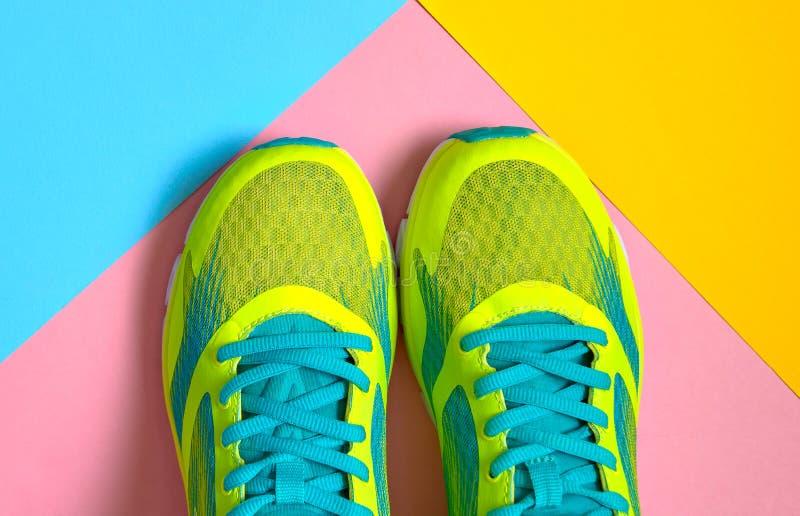 Paare Sportschuhe auf buntem Hintergrund Neue Turnschuhe auf Rosa-, Blauem und Gelbempastellhintergrund, Kopienraum lizenzfreie stockfotos