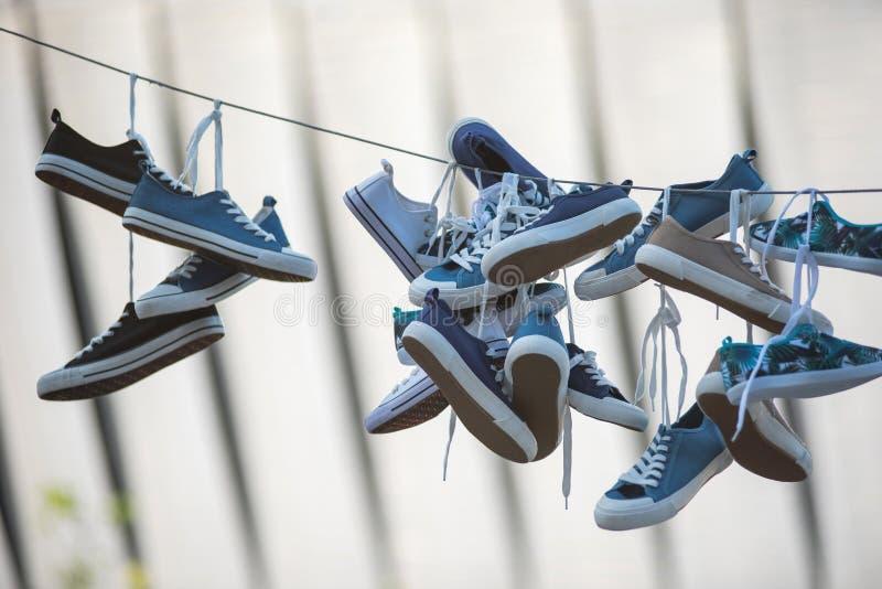 Paare Turnschuhe, die am Kabel hängen lizenzfreie stockfotografie