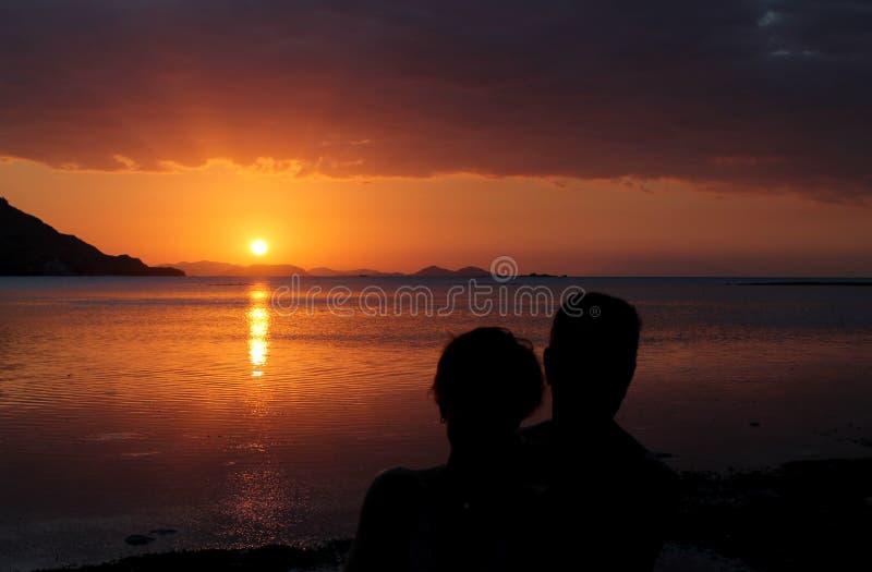 Paare umfasst vor einem schönen Sonnenuntergang durch das Meer lizenzfreie stockbilder
