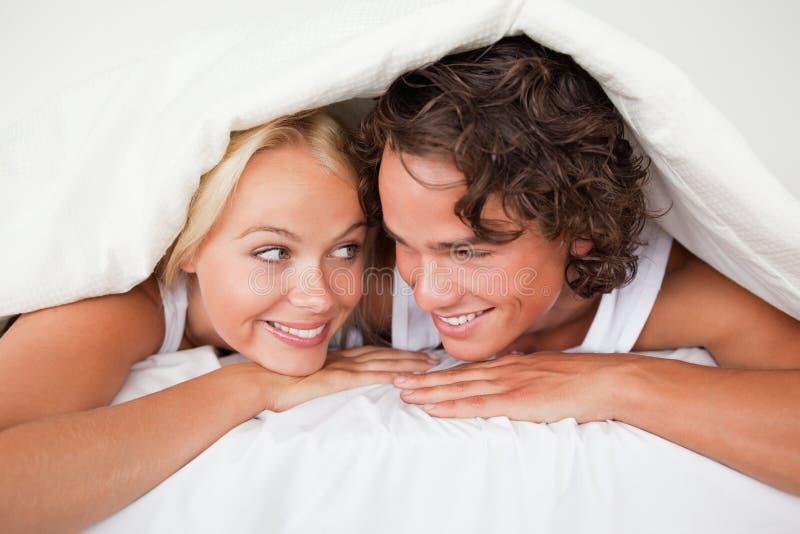 Paare unter einem Duvet mit einem wissenden Lächeln stockbilder