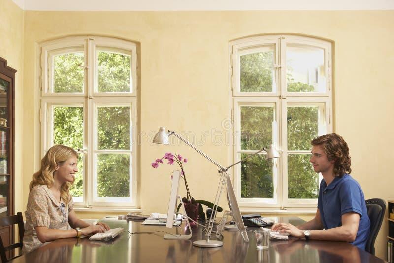 Paare unter Verwendung der Computer über Tabelle im Studien-Raum stockbild