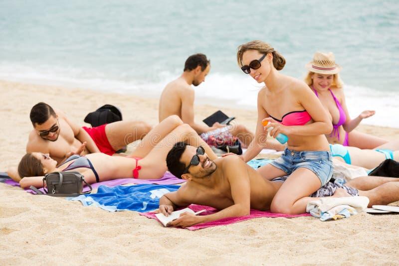 Paare unter Verwendung der Creme für Sonnenbrand stockfotografie