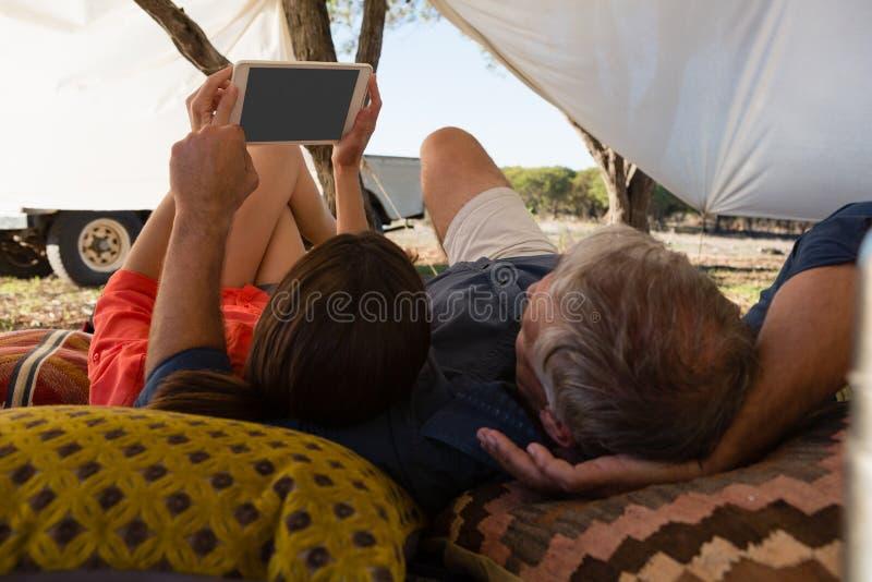 Paare unter Verwendung der Tablette im Zelt stockfoto