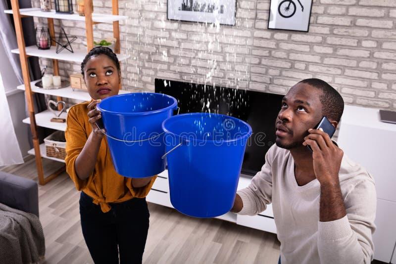 Paare unter Verwendung des Eimers f?r das Sammeln des Wasser-Durchsickerns von der Decke lizenzfreies stockfoto