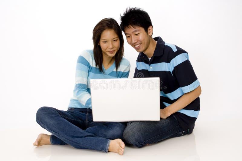Paare unter Verwendung des Laptops stockbild