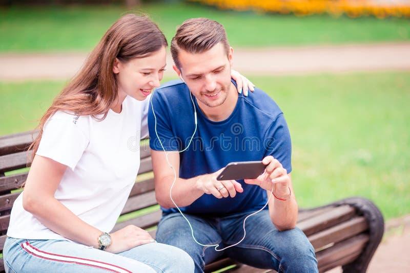 Paare unter Verwendung des Tabletten- und Mobiltelefonöffentlich Parks lizenzfreies stockbild