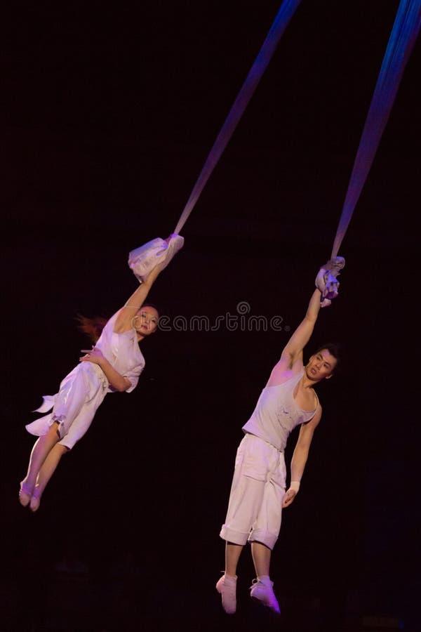 Paare von den Akrobaten, die an einem Draht hängen lizenzfreie stockfotos