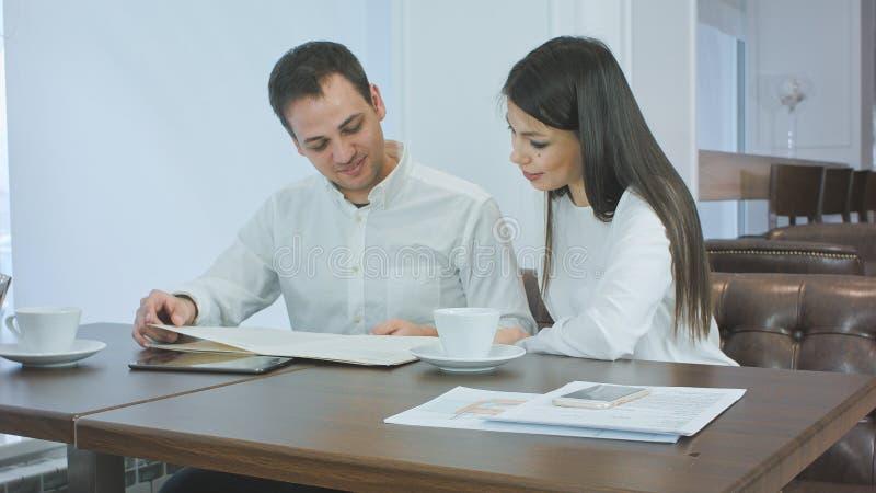 Paare von den Büroangestellten, die Menü betrachten und was entscheiden, an einer Kaffeestube zu bestellen lizenzfreie stockfotografie