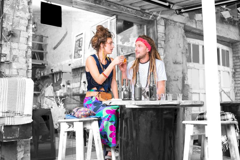 Paare von den Blumenkindern, welche die helle Kleidung klappert ihre Gläser mit Tequila tragen lizenzfreie stockbilder