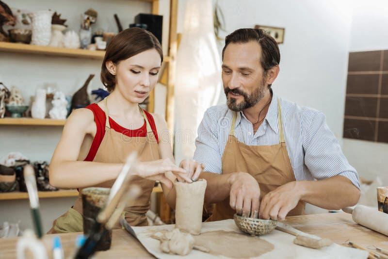 Paare von den dunkelhaarigen Ceramists, die frohes zusammenarbeiten glauben lizenzfreies stockbild