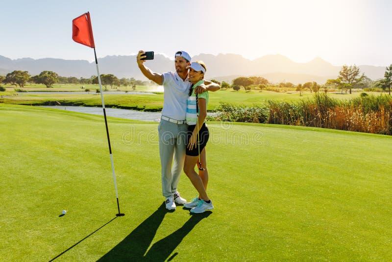 Paare von den Golfspielern, die selfie am Golfplatz machen stockfotografie