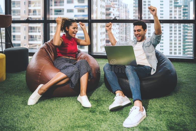 Paare von den jungen Designern, die im modernen Büro, zwei Mitarbeiter besprechen Spaßprojekt über einem Laptop, kleines Team von lizenzfreie stockbilder