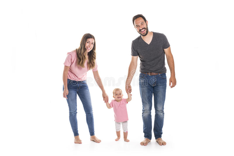 Paare von den jungen Eltern, die ihrem Baby helfen, erste Schritte auf Boden in ihrem Haus zu machen stockfotografie