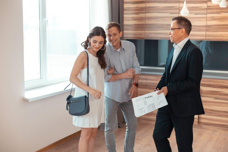Paare von den jungen Geschäftsmännern, die nahe Grundstücksmakler stehen lizenzfreie stockfotos