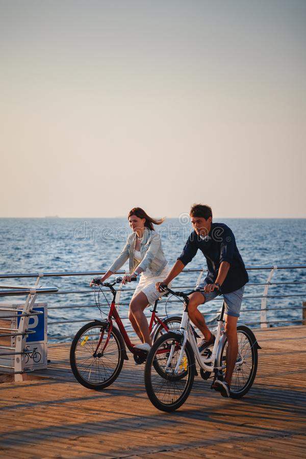 Paare von den jungen Hippies, die zusammen am Strand am Sonnenaufganghimmel zur hölzernen PlattformSommerzeit radfahren lizenzfreies stockbild