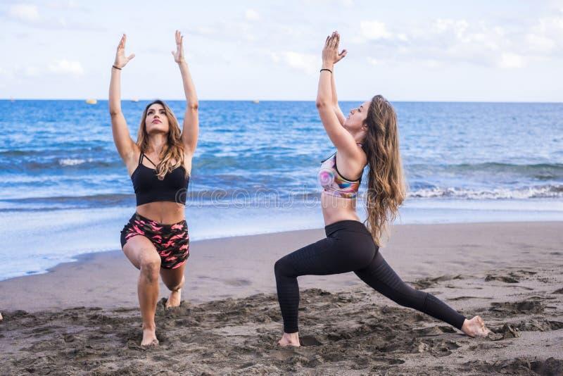 Paare von den kaukasischen jungen Frauen des schönen Modells, die pilates am Strand in der freien Freizeitbetätigung tun netter L lizenzfreie stockfotos