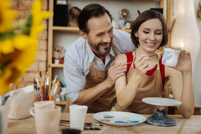 Paare von den lachenden Ceramists beim Scherzen bei Arbeit stockbild