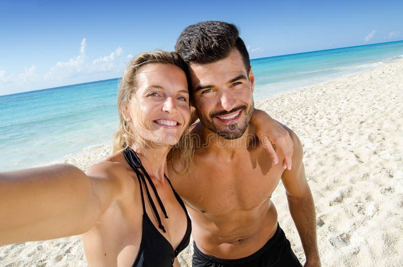 Paare von den Liebhabern, die selfie Foto am Strand machen stockfotografie