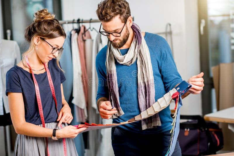 Paare von den Modedesignern, die am Studio arbeiten lizenzfreies stockfoto