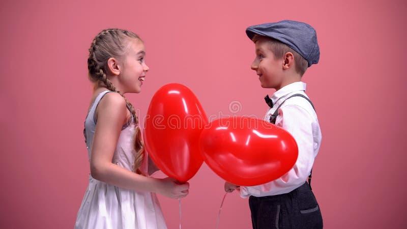 Paare von den netten Kindern, die rote Herz-förmige Ballone, Valentinsgrußtagesgeschenk austauschen lizenzfreie stockfotografie