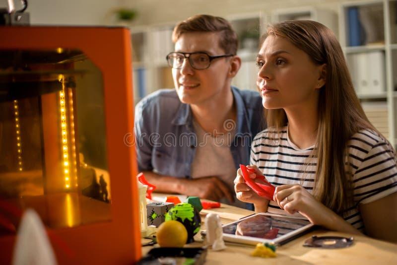 Paare von den Studenten, die Drucker 3D verwenden lizenzfreies stockfoto