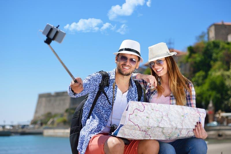 Paare von den Touristen, die ein selfie in einer Stadtstraße fotografieren stockfotos