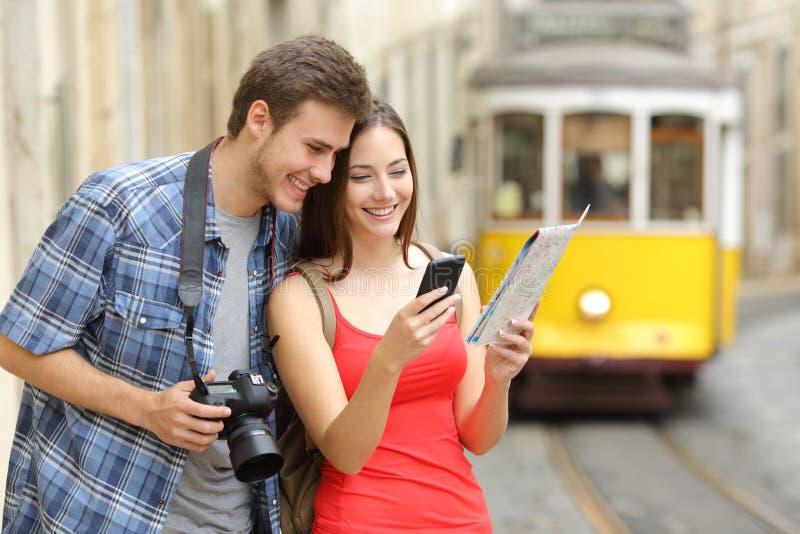Paare von den Touristen, die online Führer konsultieren stockfotografie