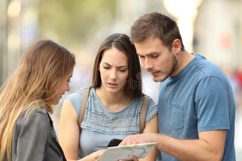 Paare von den Touristen, die um Hilfe auf der Straße bitten stockfotografie