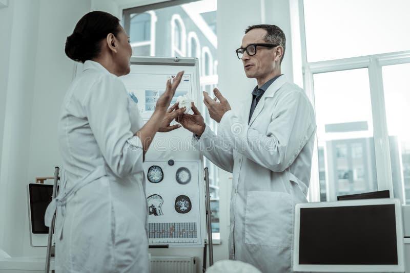 Paare von ernsten bei der Diskussion ausdrucksvoll gestikulierenden Doktoren stockfoto