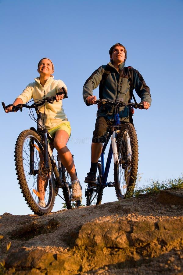 Paare von Fahrrädern auf Sonnenuntergang lizenzfreies stockbild
