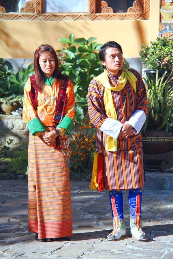 Paare von jungen Tänzern in den bunten traditionellen Stoffen von Bhutan stockfoto