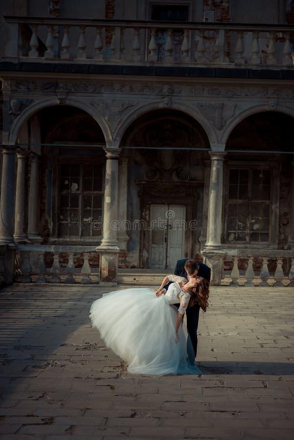 Paare von Jungvermählten küssen während ihres Tanzes auf dem Balkon des alten Palastes Vertikales Porträt in voller Länge lizenzfreies stockbild