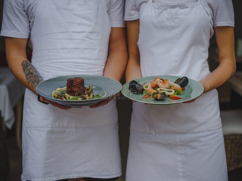 Paare von Kellnerhalteplatten Kellner- und Kellnerinumhüllungslebensmittel auf einem unscharfen Hintergrund Klassisches Restauran stockfotografie
